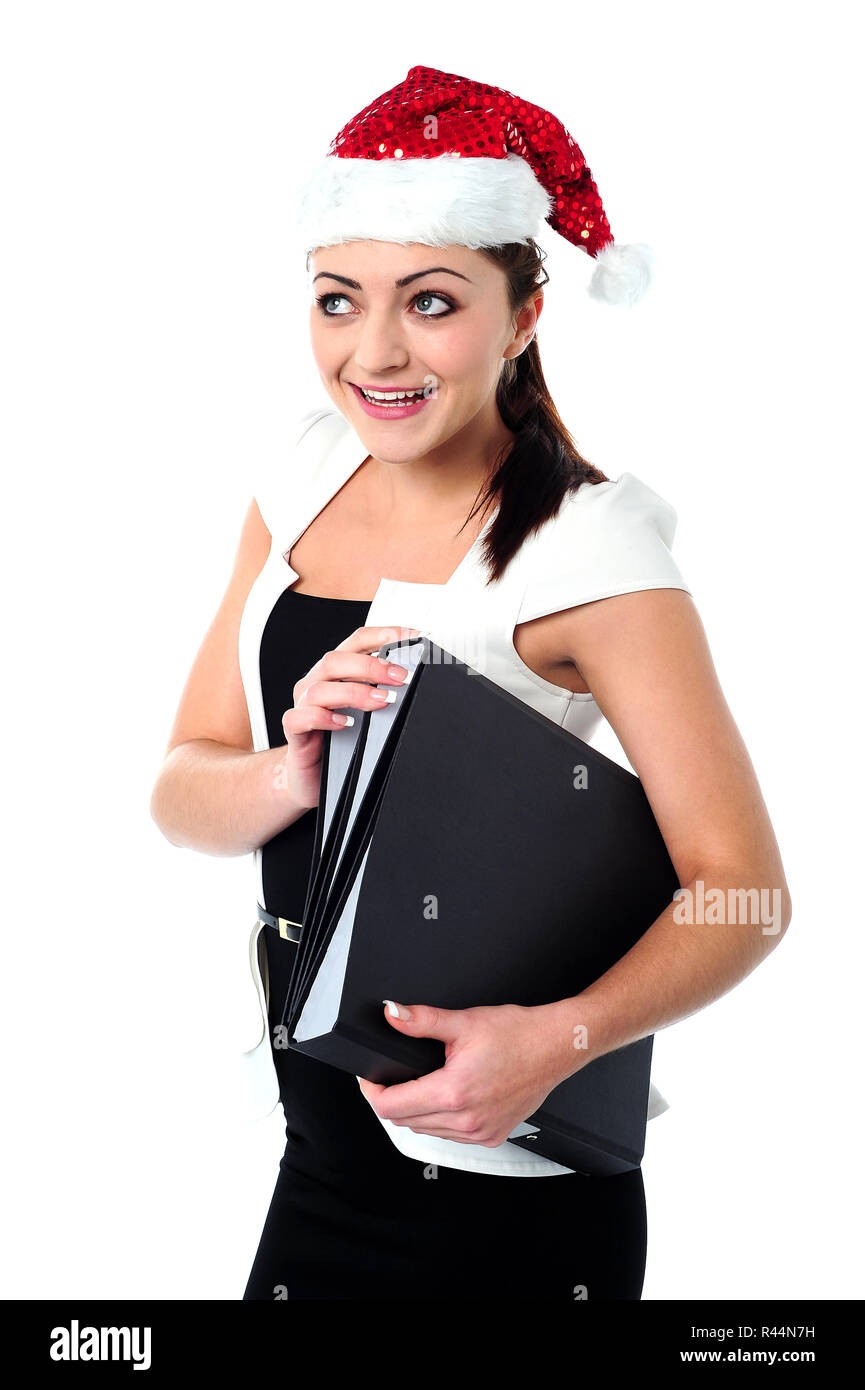 Female employee holding files wearing santa cap - Stock Image