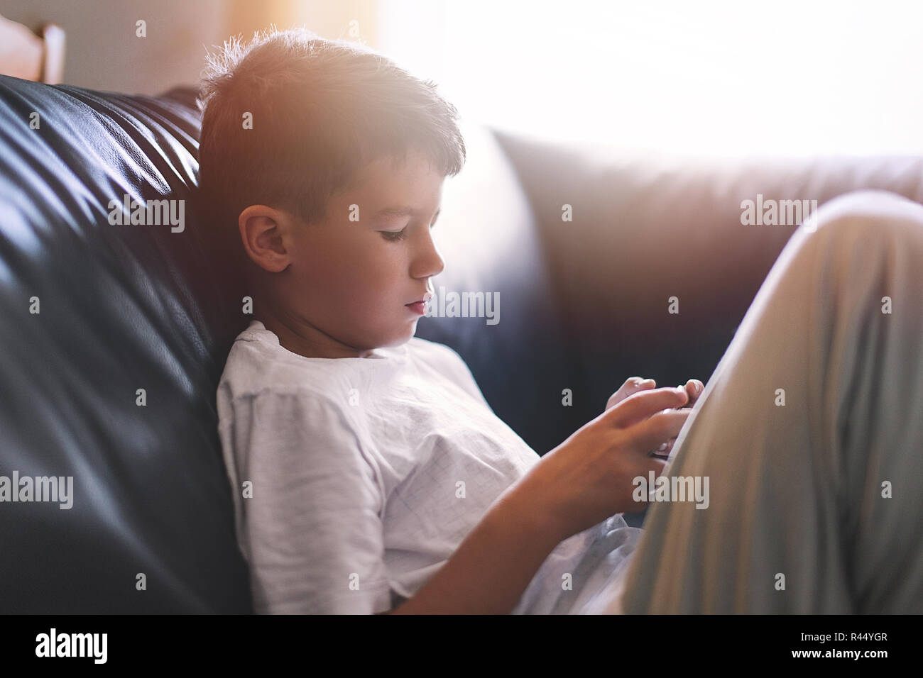 Little lonely boy playing on smartphone on sofa at home - Stock Image