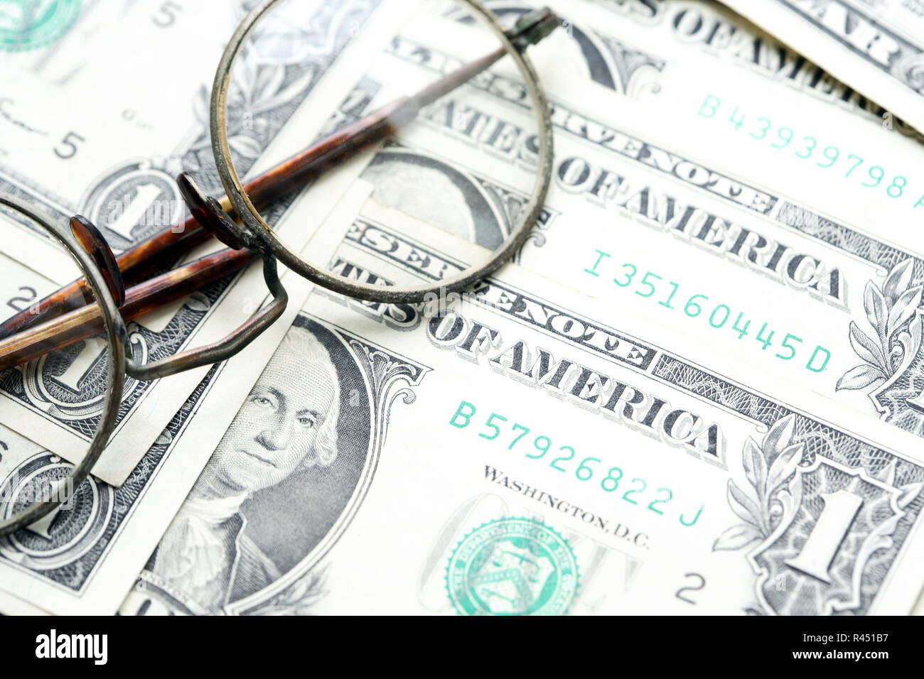 Retro bookkeeping concept. Old spectacles on dollar cash background