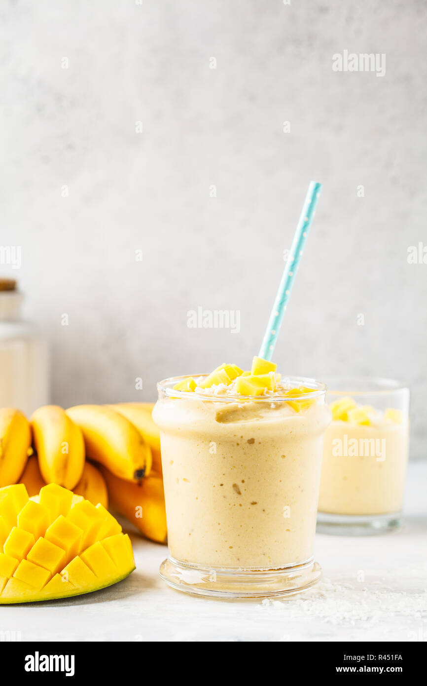Mango banana smoothie with coconut in a jar. Plant based food concept. - Stock Image