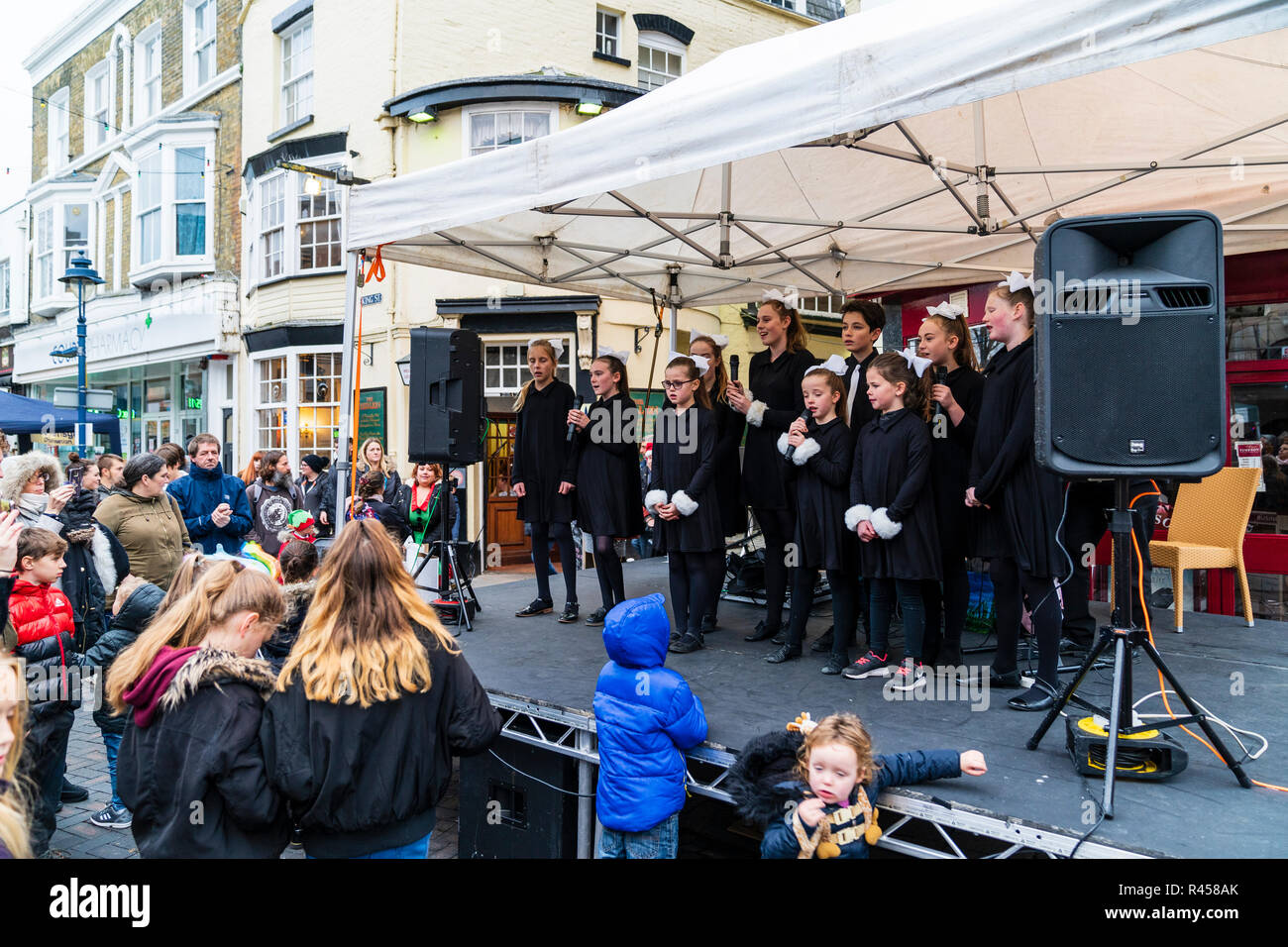 Children, girls, age 8-14 years, from the Kent Show Choir singing on outdoor stage in front of small audience during Christmas event at Ramsgate town. Girls dressed in black with white double bows on head. Stock Photo