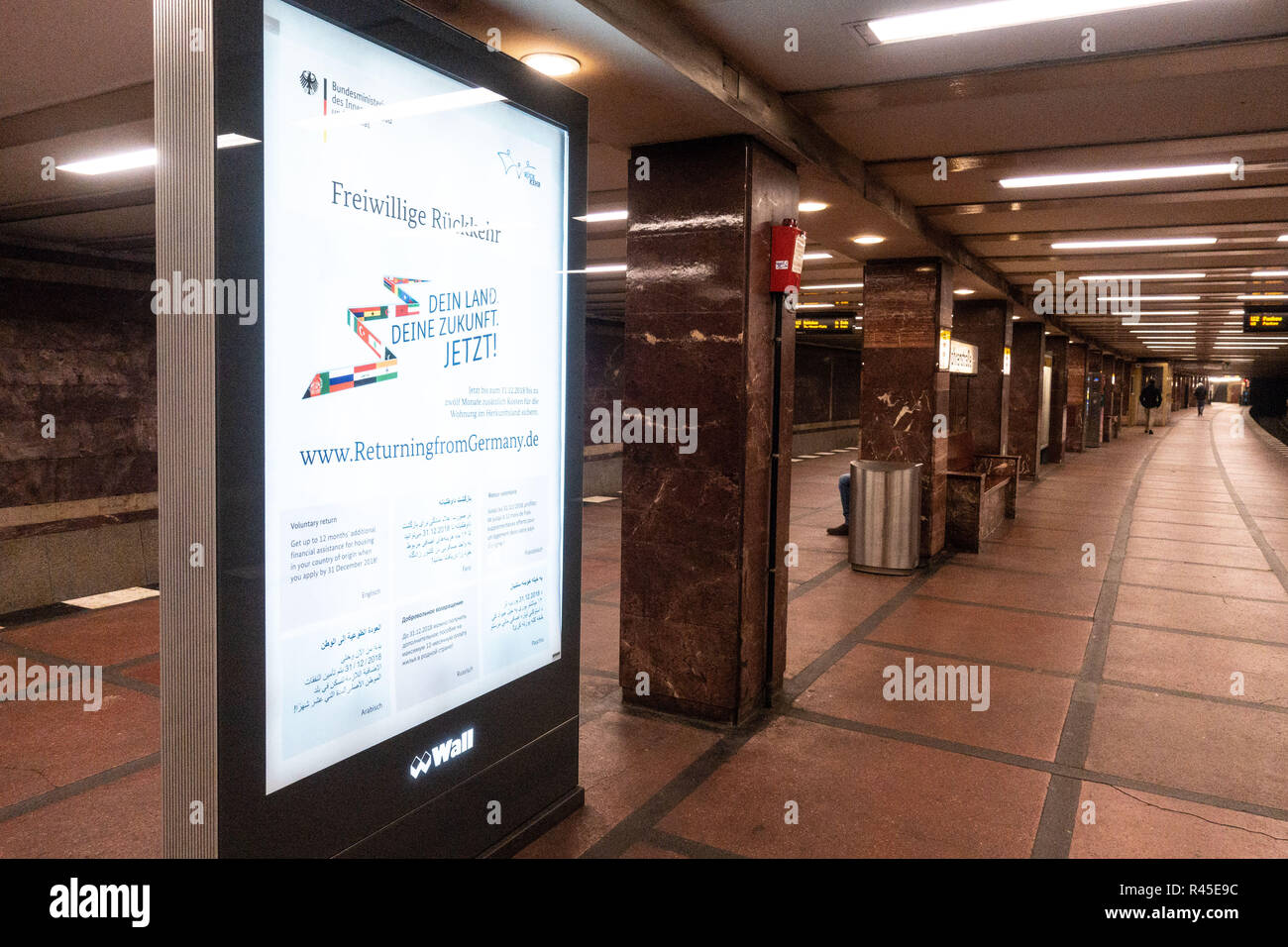 Berlin, Berlin, Germany. 24th Nov, 2018. A campaign poster by the German Ministry of the Interior, promotes the voluntary return of refugees to their home countries is seen at a metro underground station in Berlin, Germany, November 24, 2018. The Federal Office for Migration and Refugees (Bundesamt für Migration und Flüchtlinge or BAMF), initiated a campaign encouraging refugees to return to their source countries, through several advertising mediums, one of which as street posters. Credit: Omer Messinger/ZUMA Wire/Alamy Live News - Stock Image