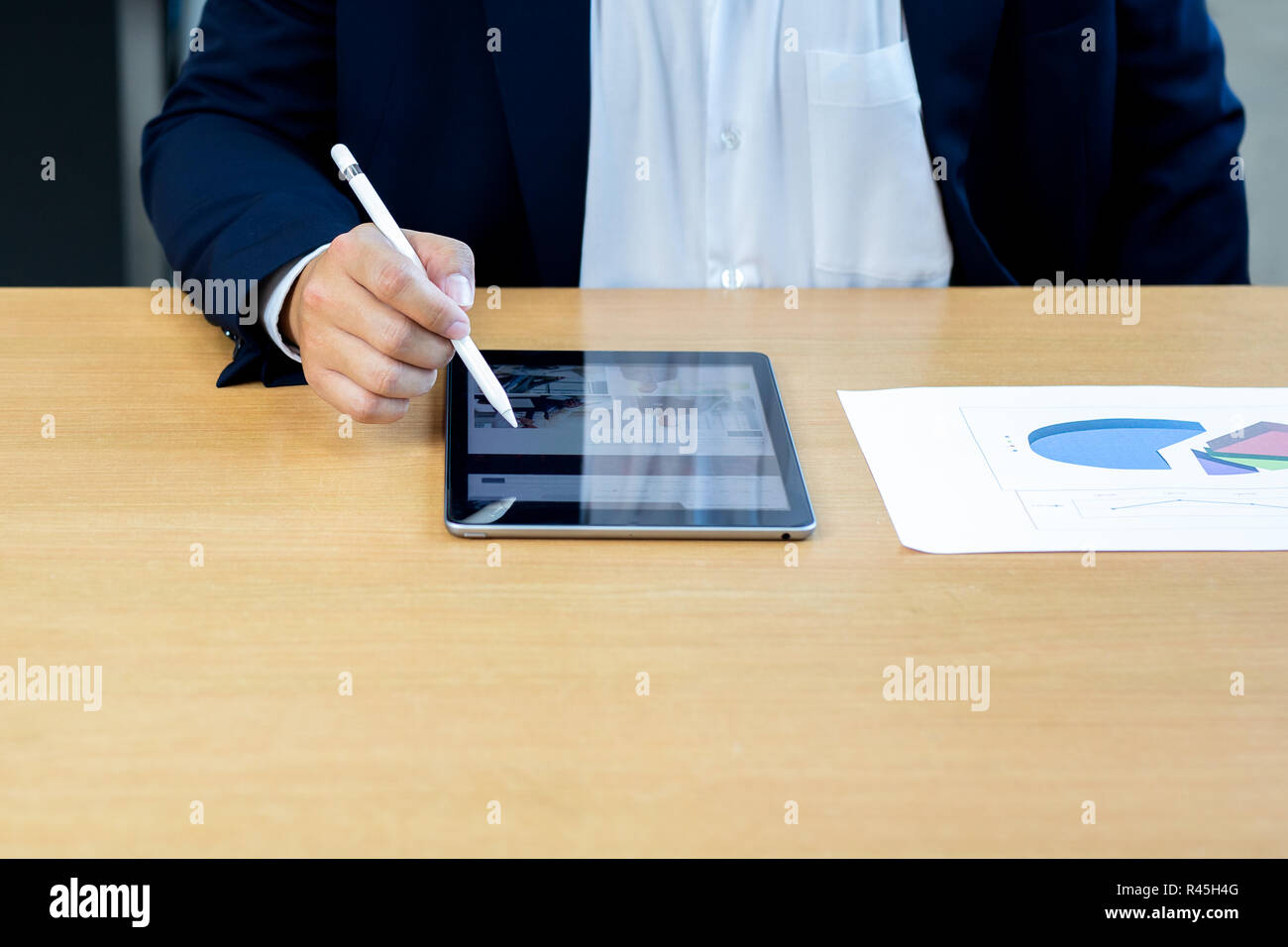 Businessman using digital tablet pen on notped with paper stock chart on desk. - Stock Image