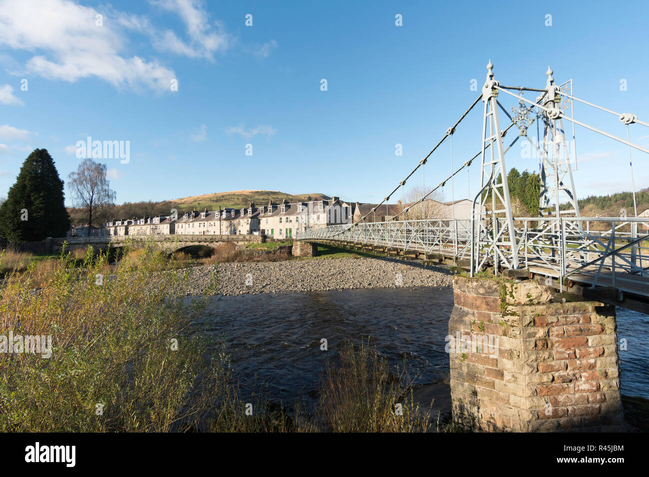 The listed Victorian suspension footbridge, the Boatford Bridge, over the river Esk, Langholm, Dumfries and Galloway, Scotland, UK - Stock Image