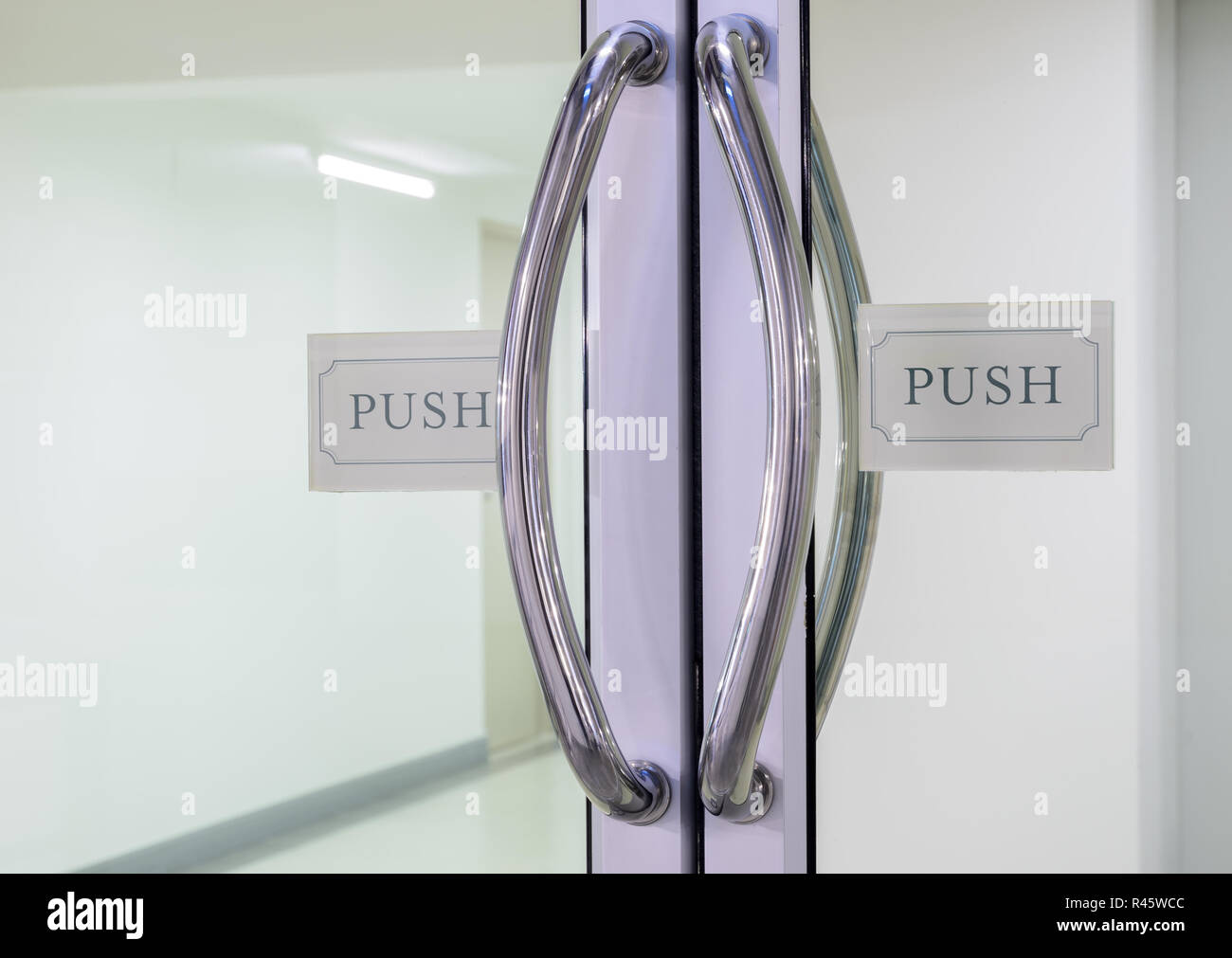 Chrome handles with push sign on glass door - Stock Image