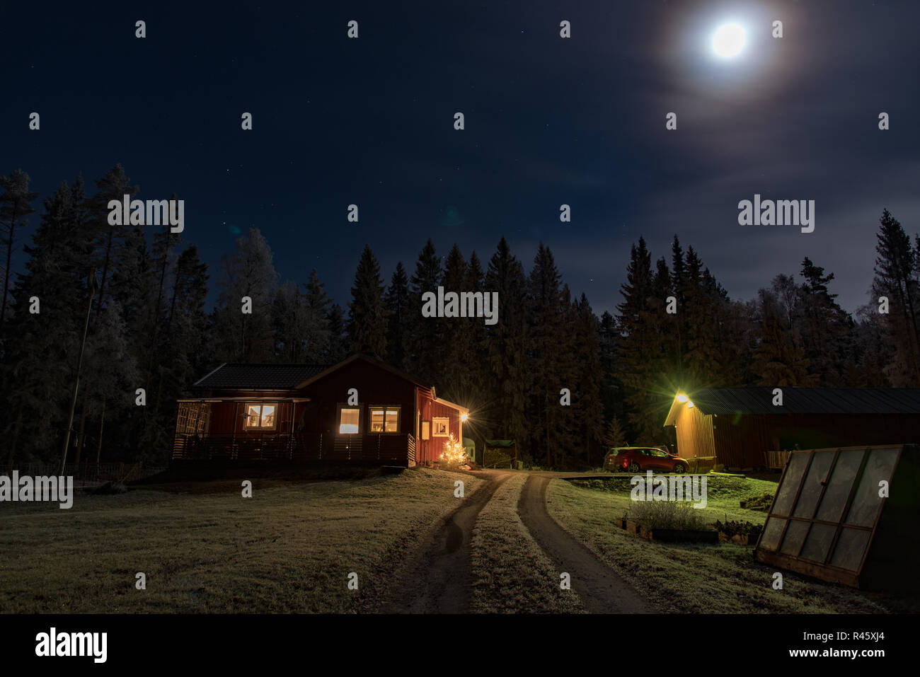 full moon shining over a little red cabin in a swedish forest - Stock Image