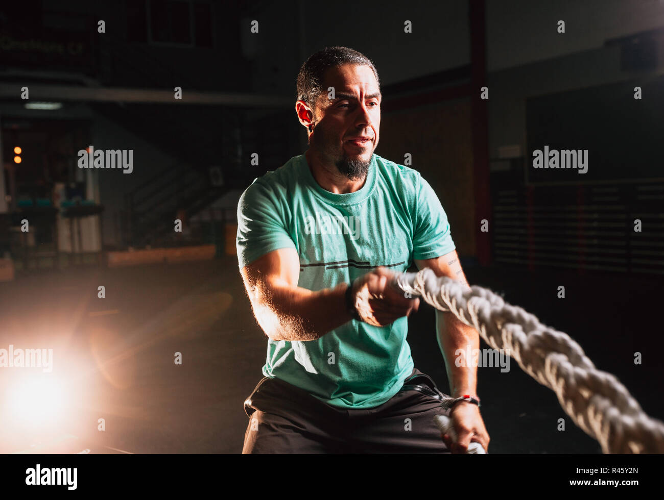 Athletic young man doing some cross-fit exercises with a rope indoor - Stock Image
