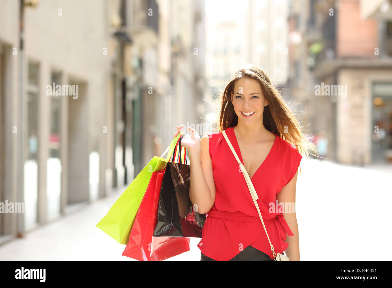 Front view portrait of a happy shopper walking towards camera holding shopping bags looking at you - Stock Image