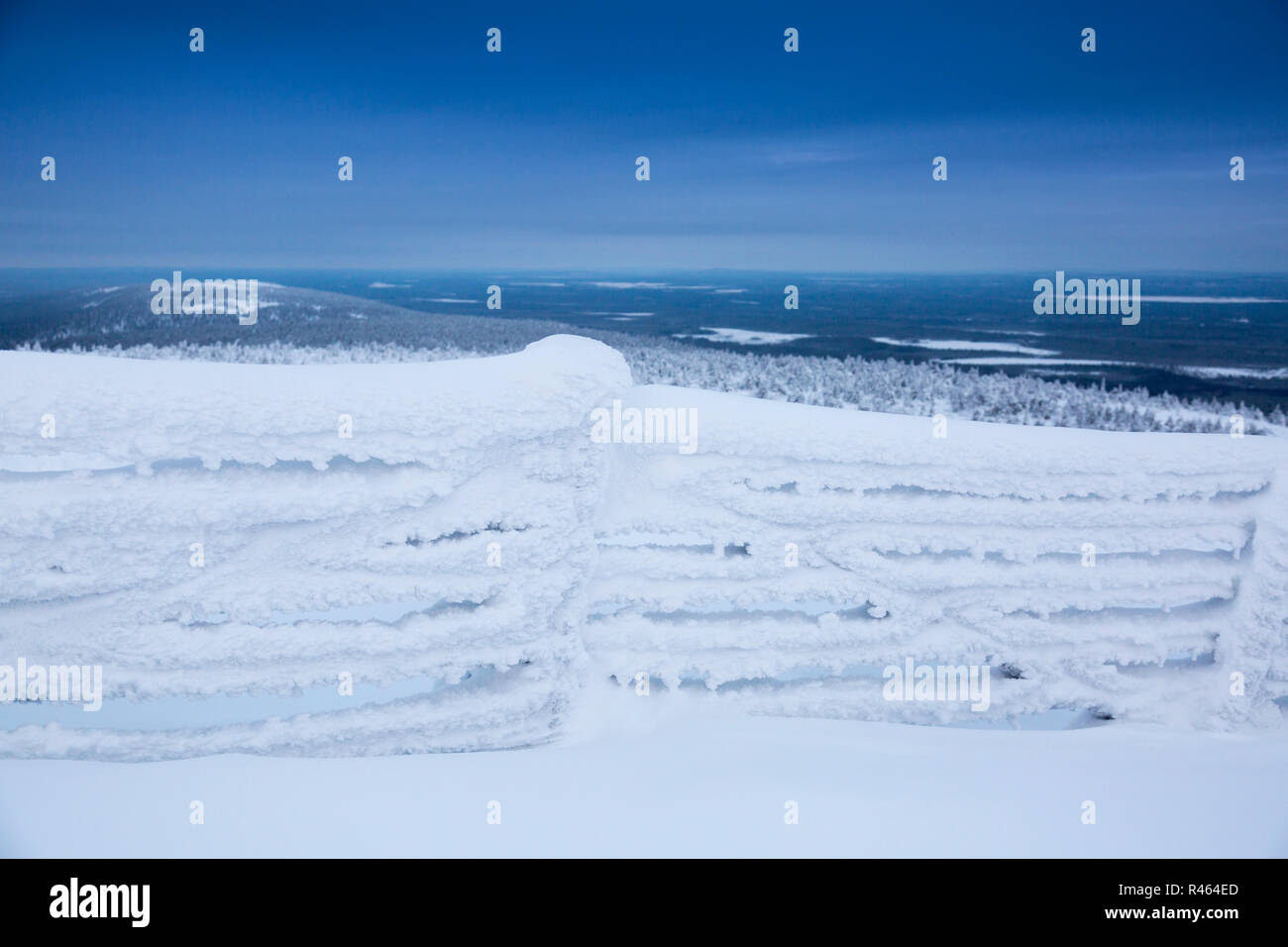 frozen fence covered with snow against mountains background Stock Photo