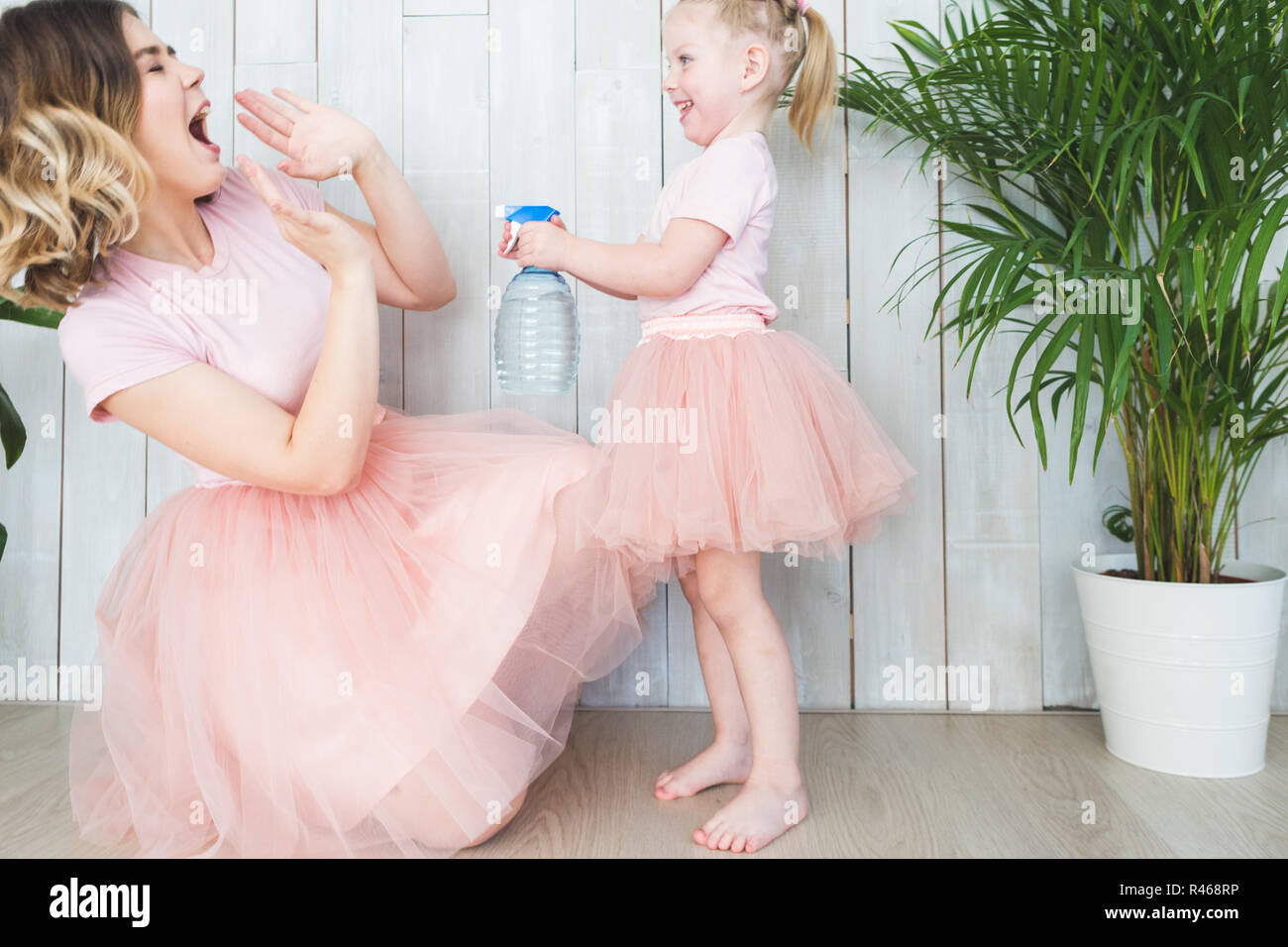 Cute little girl and her mom playing next to plants in pots on a white background. - Stock Image