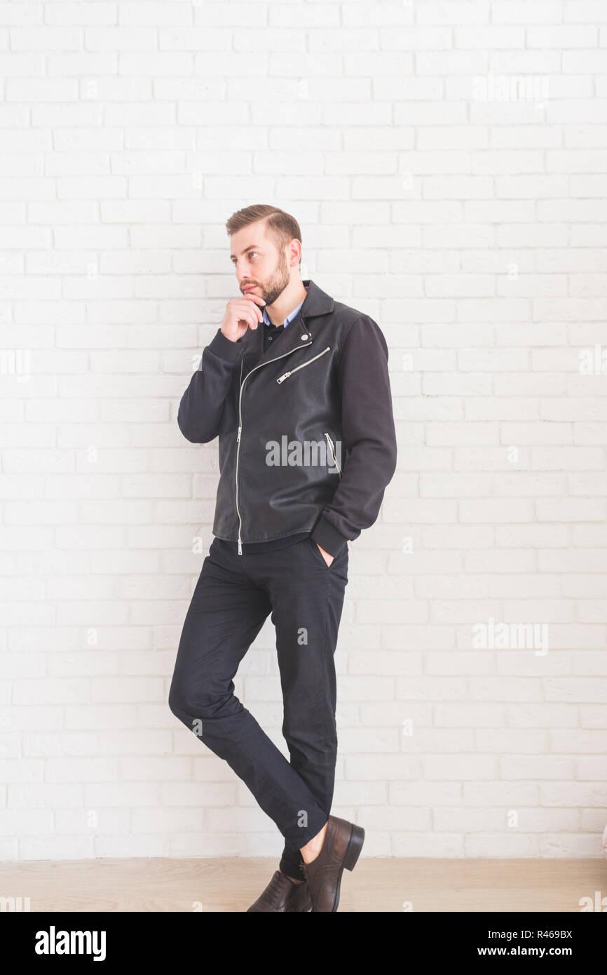 Young stylish man in black jacket on white background. - Stock Image