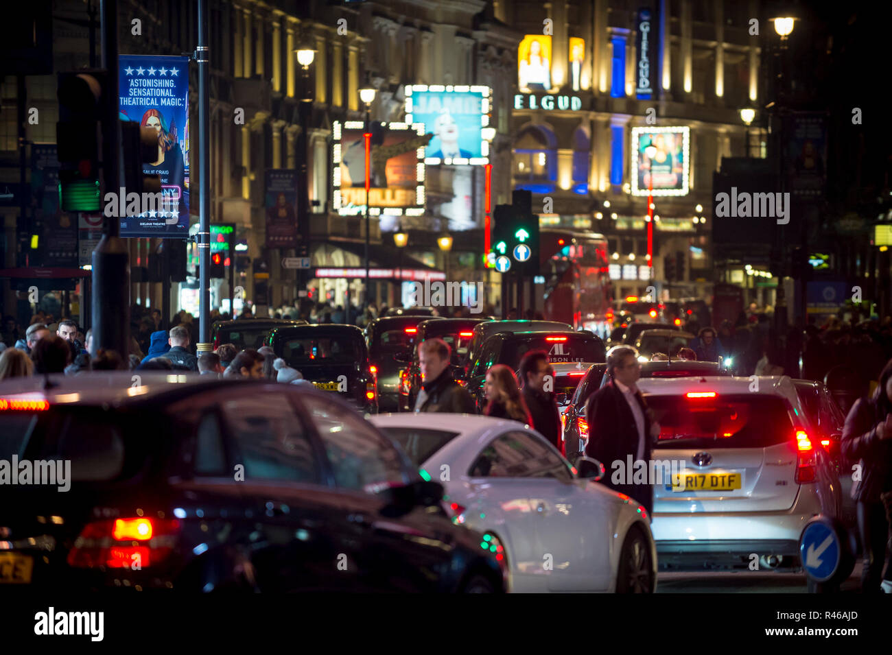 LONDON - DECEMBER 23, 2018: Pedestrians cross a traffic-clogged intersection at Piccadilly Circus in front of the shining lights of West End theatres. - Stock Image