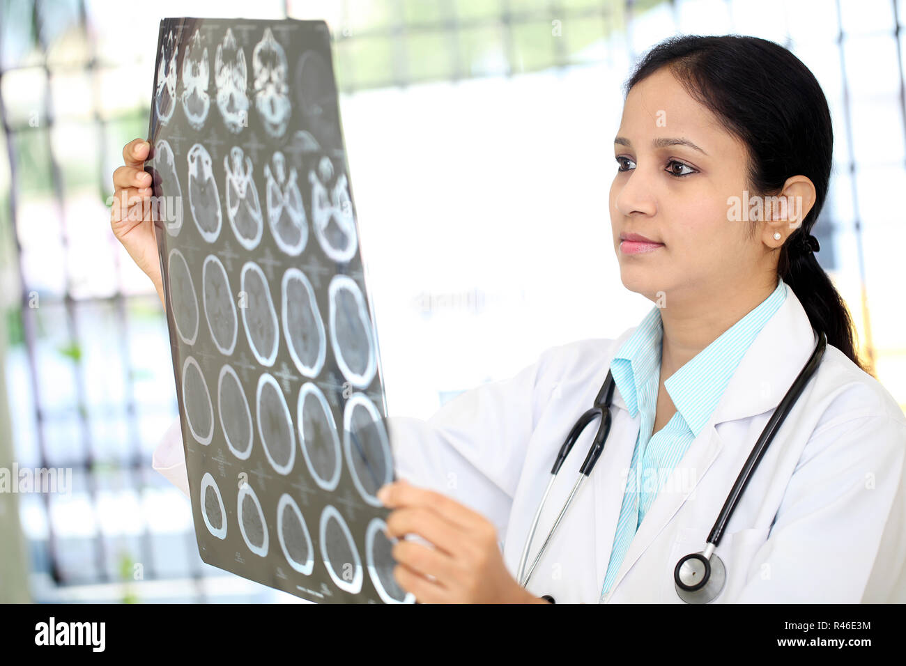 Female doctor examining a brain computerized tomography scan - Stock Image