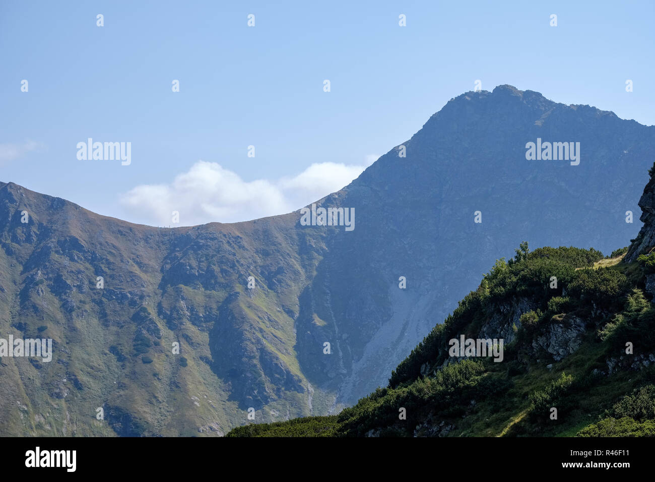 Distant mountain cores in mist in slovakia Tatra mountain trails in clear autumn day with blue sky and green vegetation - Stock Image