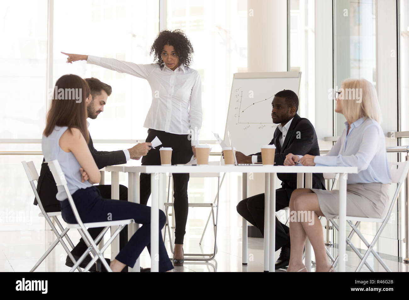 Angry mixed-race manager firing incompetent employee asking to l - Stock Image