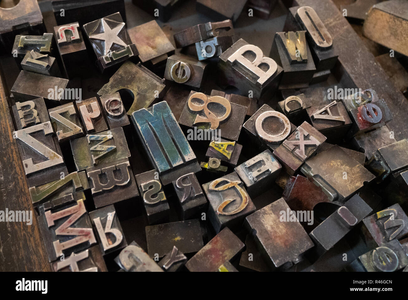 Jumble of different metal letters in a tray for use in an old Heidelberg printing press. - Stock Image