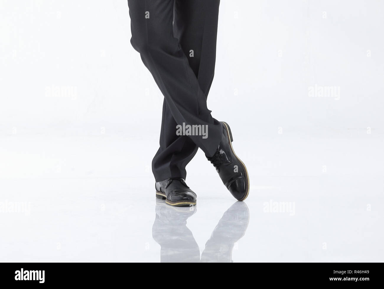 crossed legs of business man in pants and shoes.isolated on white - Stock Image