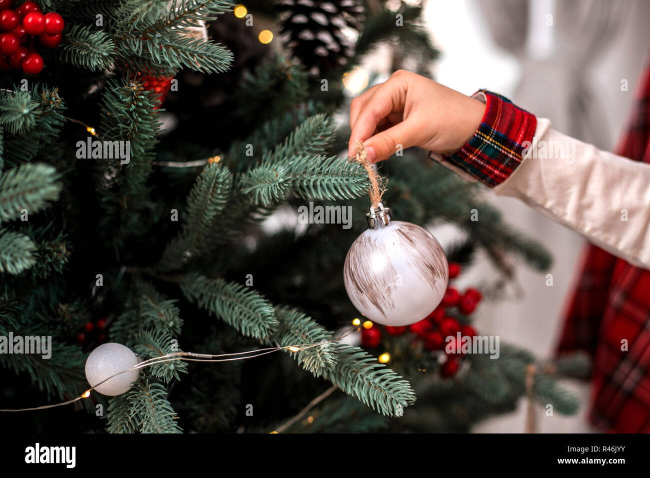 Little child's hand decorating Christmas tree indoors. - Stock Image