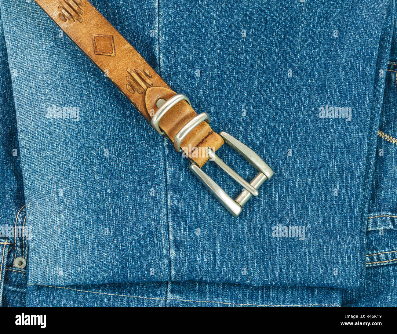 Vintage leather belt with buckle on old blue jeans background - Stock Image