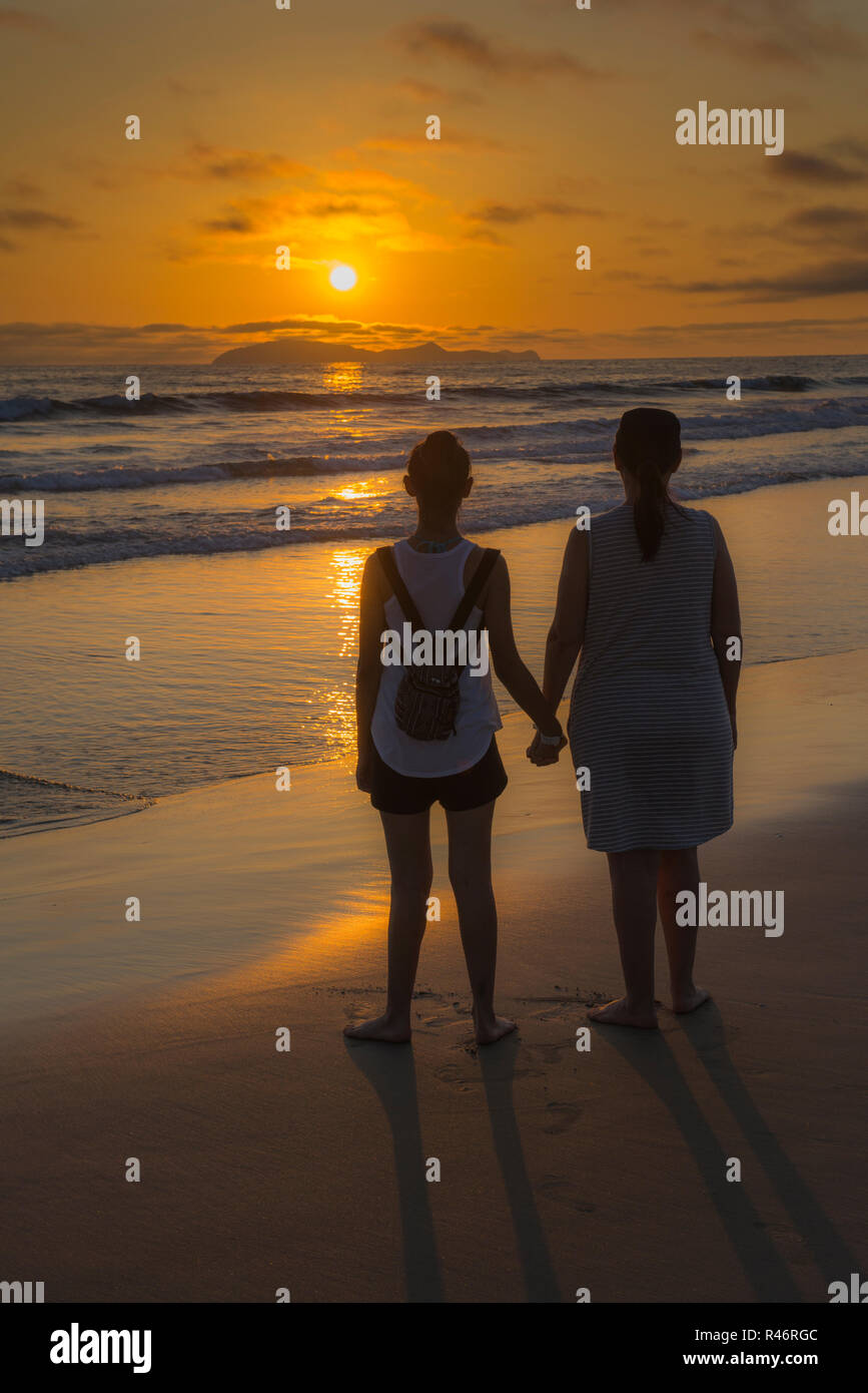 Unplugged daughter and mother watching a beautiful sunset in Rosarito Baja California. Mexico. - Stock Image