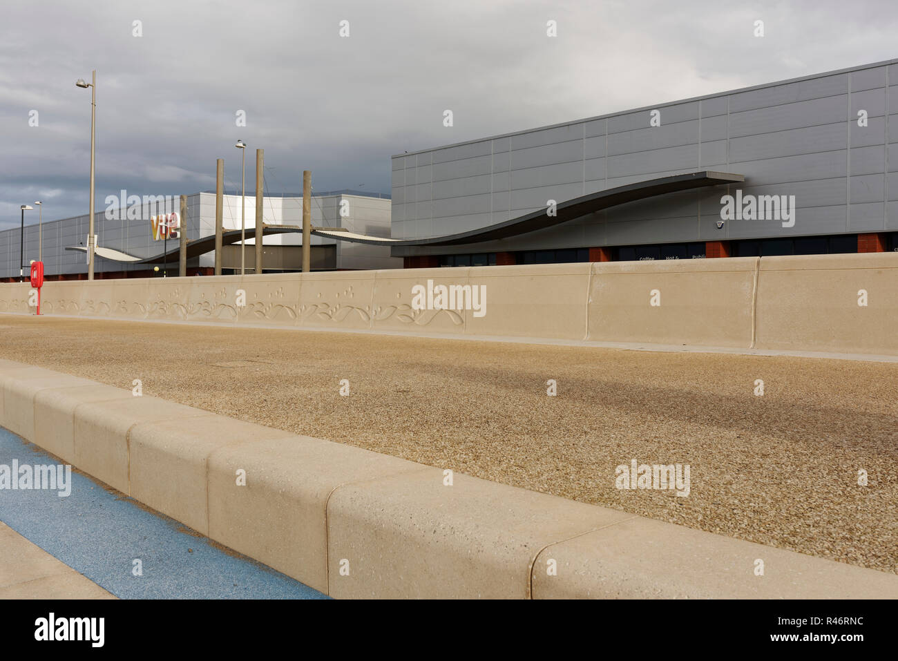 Concrete coastal flood protection and sea wall on cleveleys promenade with aluminium clad buildings in the background on the fylde coast in lancashire Stock Photo