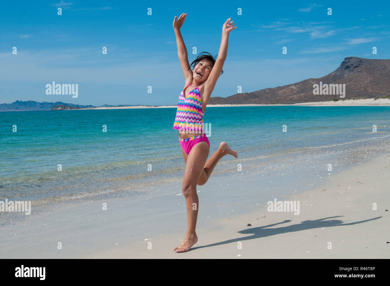 Unplugged. Teenager is running happy on the beach, unplugged of cel phones tablets and electronic devices. - Stock Image