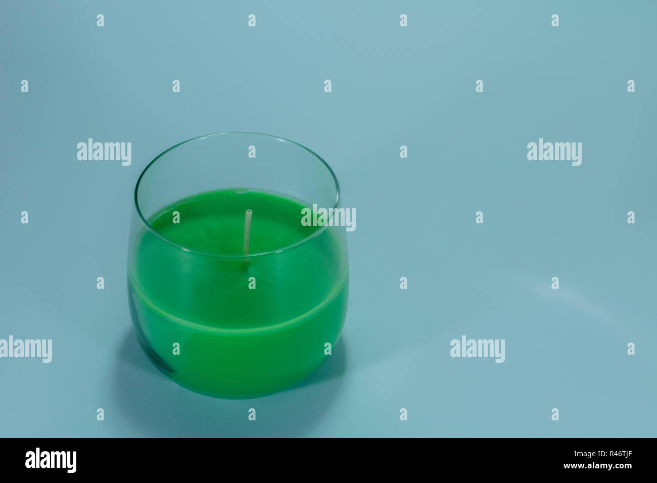 Green candle on isolated white background - Stock Image