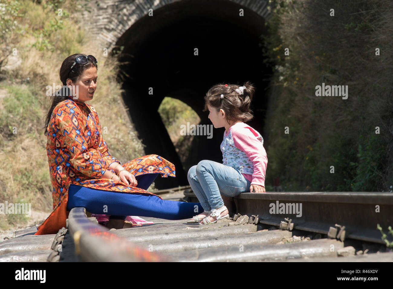 Mother and daughter sitting on a rail track, talking. - Stock Image