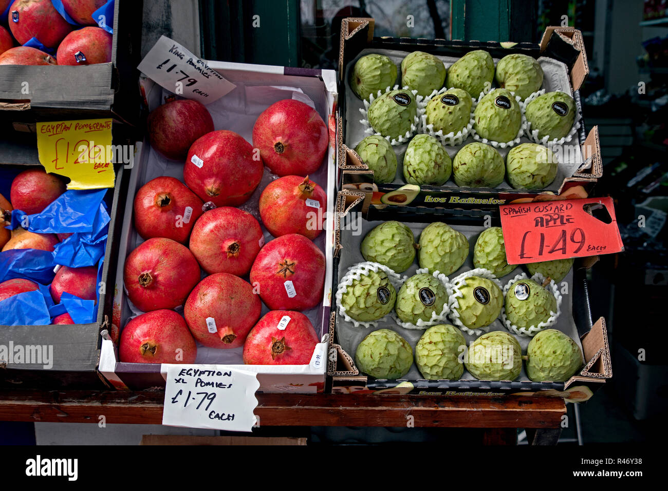 Pomegranates and custard apples on display outside a greengrocer's shop in Tollcross, Edinburgh, Scotland, UK. - Stock Image