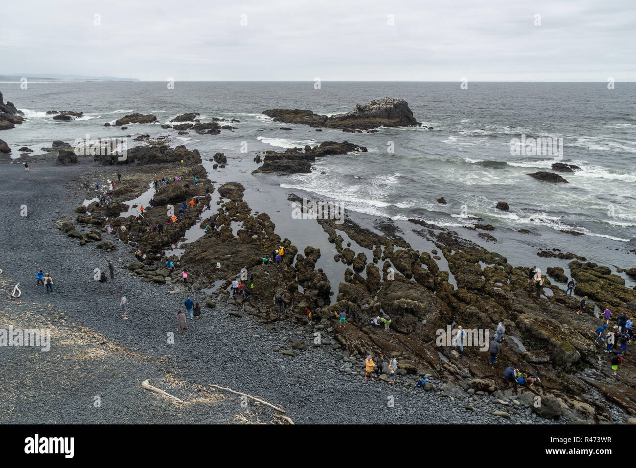 Cobble Beach with people enjoying the tide pools, Yaquina Head Outstanding Natural Area, Newport, Oregon Coast, USA. - Stock Image
