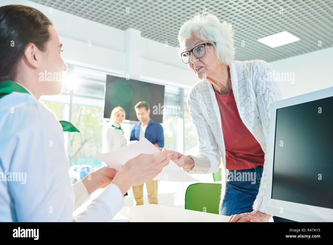 Outraged senior lady speaking loudly in travel agency office - Stock Image