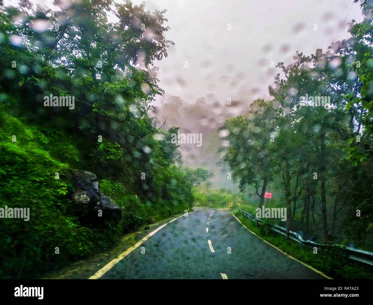 Driving down the mountain road in the rain, rain drops on the windscreen - Stock Image