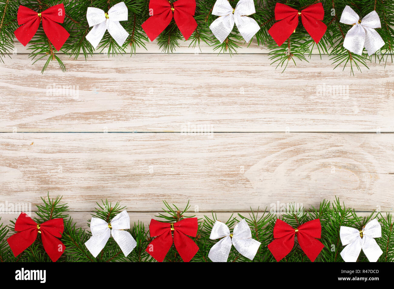 Christmas frame made of fir branches decorated with bows on a light wooden background - Stock Image