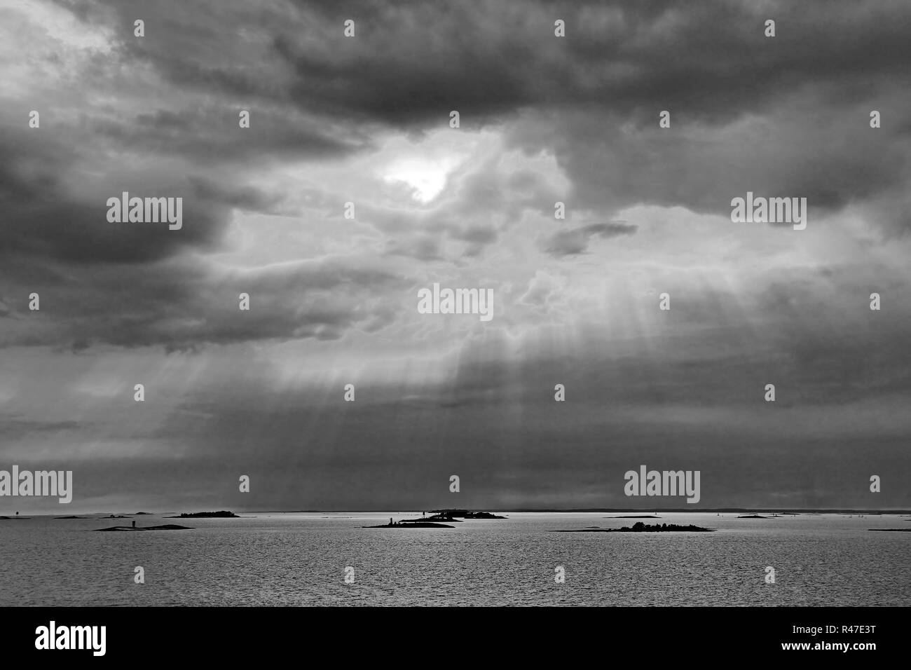 The sun behind the clouds with rays of light shining down on sea - Stock Image
