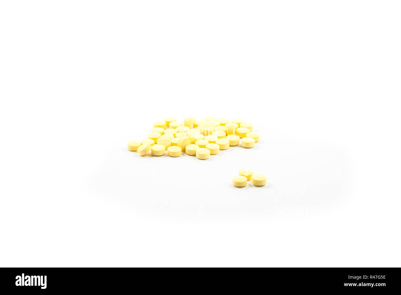 Yellow pills isolated on white background - Stock Image