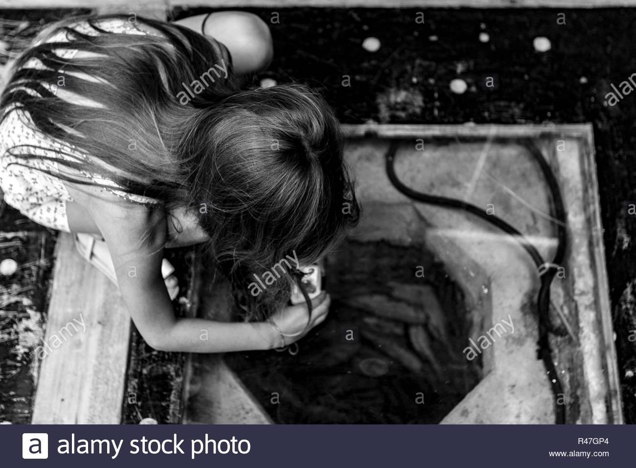 Bozcaada Summer 2015 photos by Hulki Okan Tabak. Young girl photographing through a glass tile where below lies an old cellar. - Stock Image