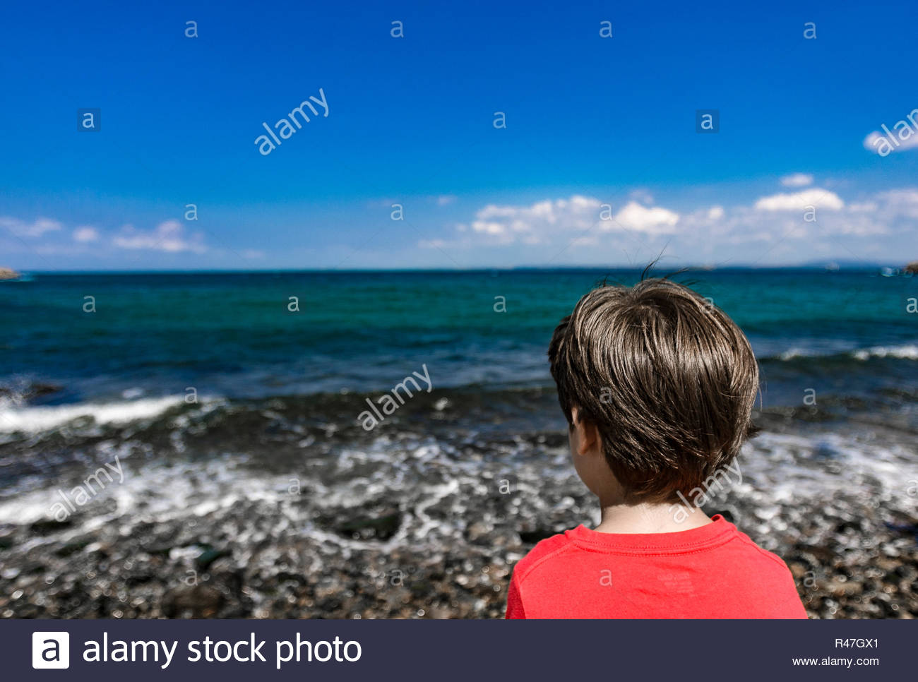 Bozcaada Summer 2015 photos by Hulki Okan Tabak. Lonely boy looking out, beach, blue sea, clear sky and waves. - Stock Image