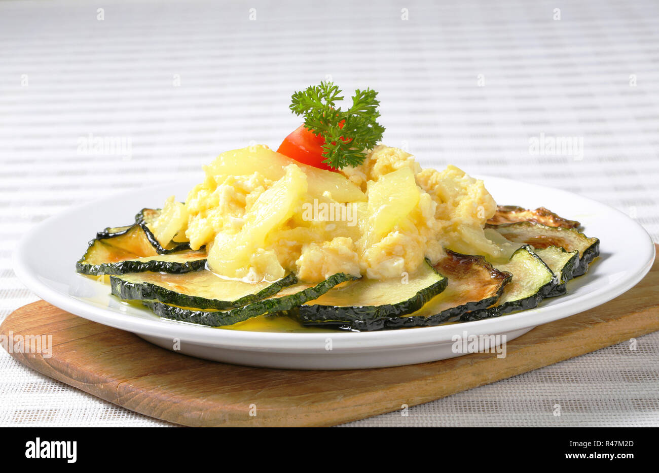 Roasted zucchini with potato egg scramble - Stock Image