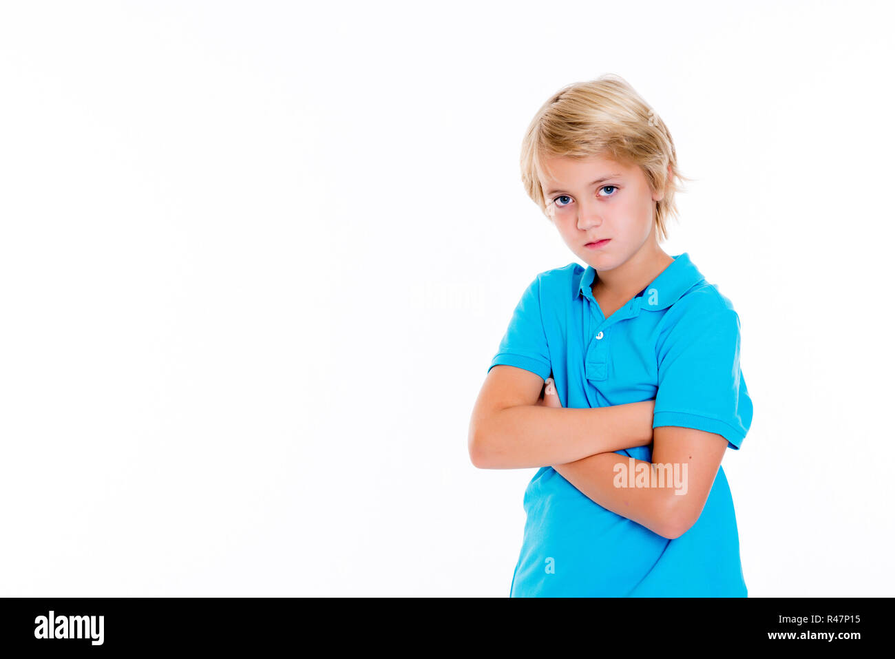 bearish blond boy with crossed arms - Stock Image