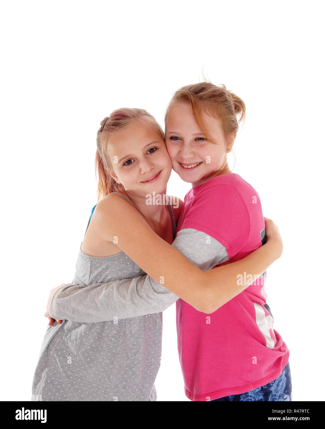 Smiling sisters hugging each other. - Stock Image