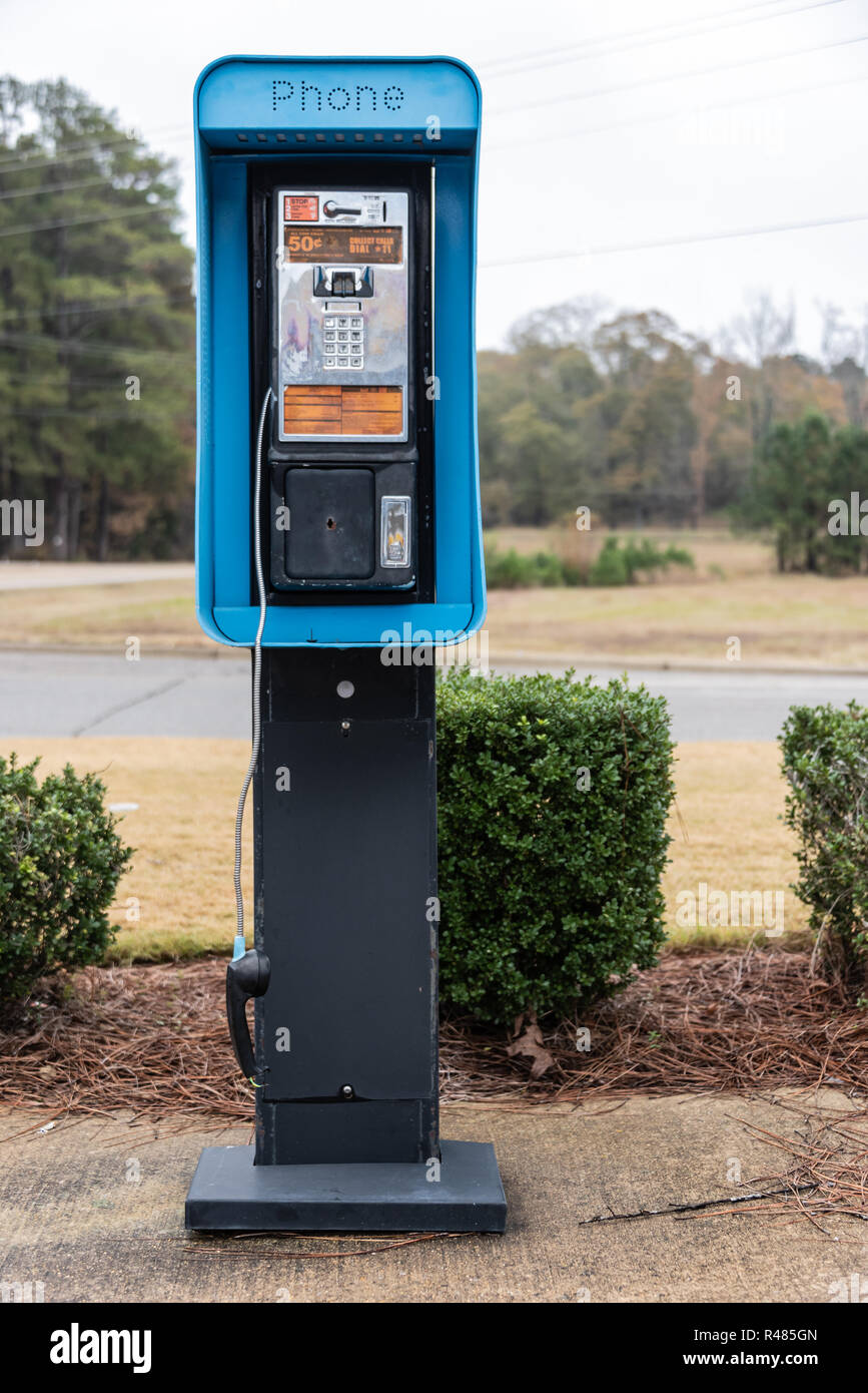 Outdoor public pay phone with dangling broken handset in Tupelo, Mississippi. (USA) - Stock Image