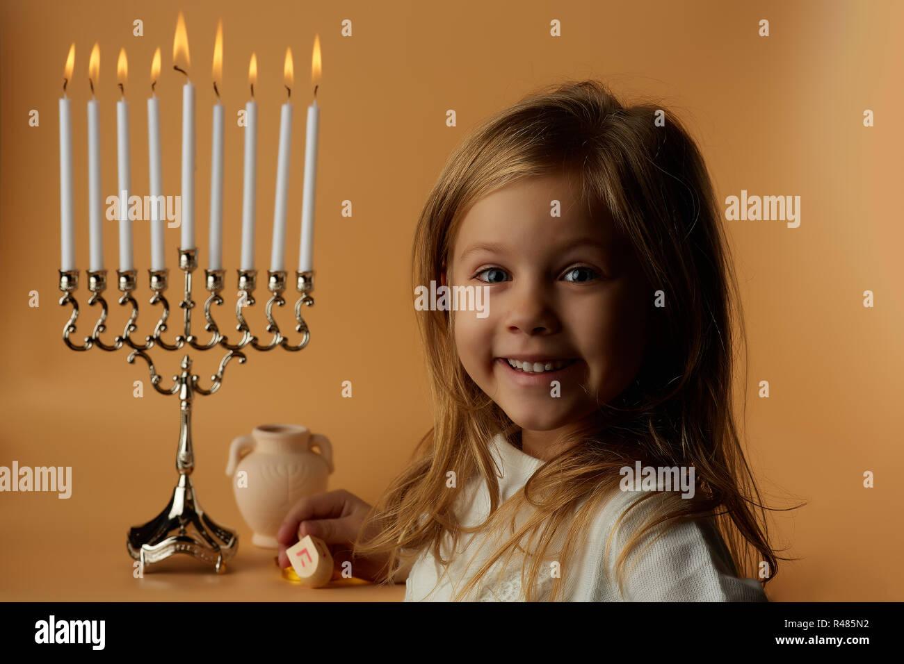 Hanukkah: Little girl on the background of candles Hanukkah - Stock Image