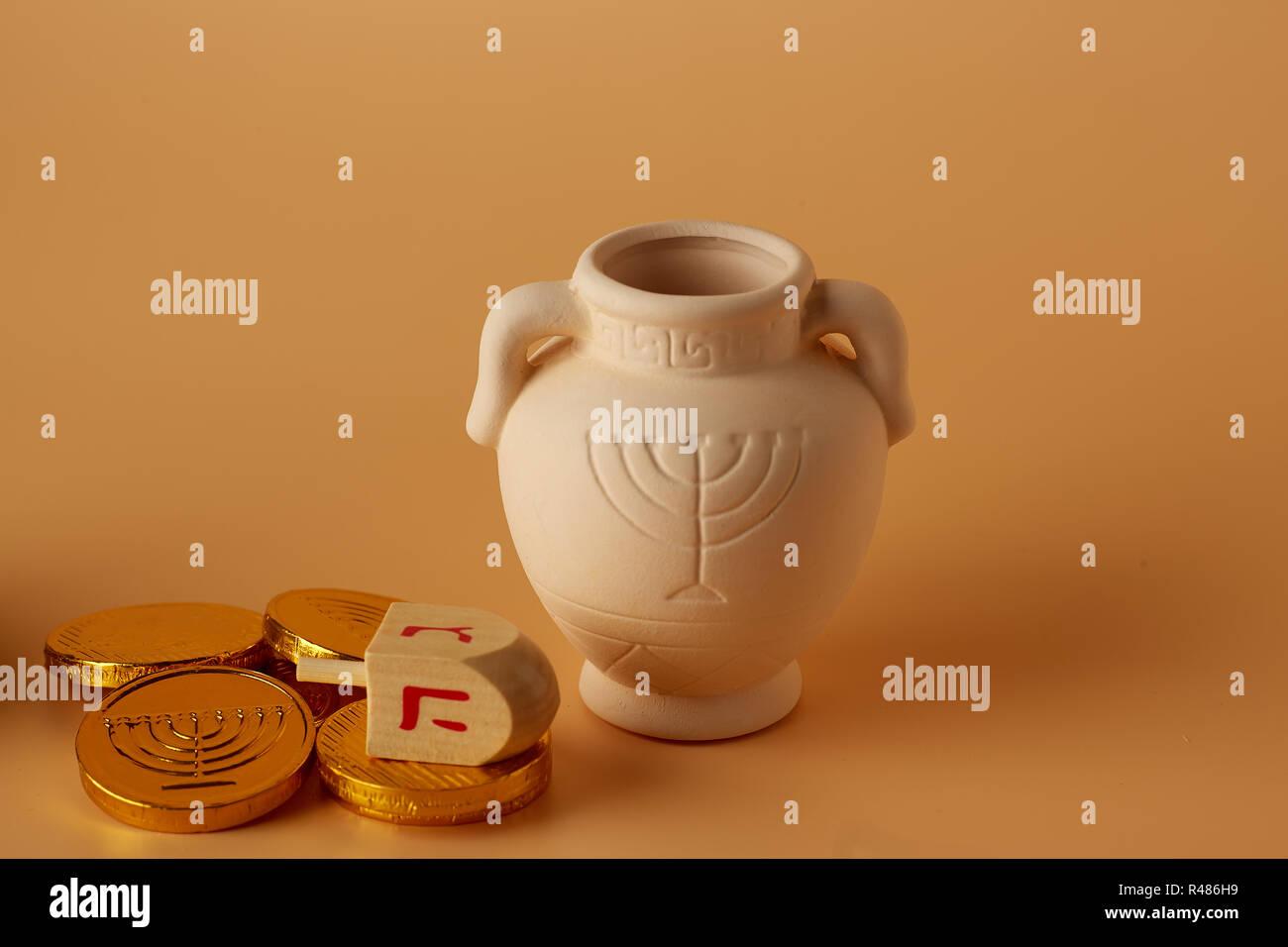 ah gelt or money or coins with Hanukkah dreidel and a Hanukkah clay jug . Translation: Happy Holidays - Stock Image