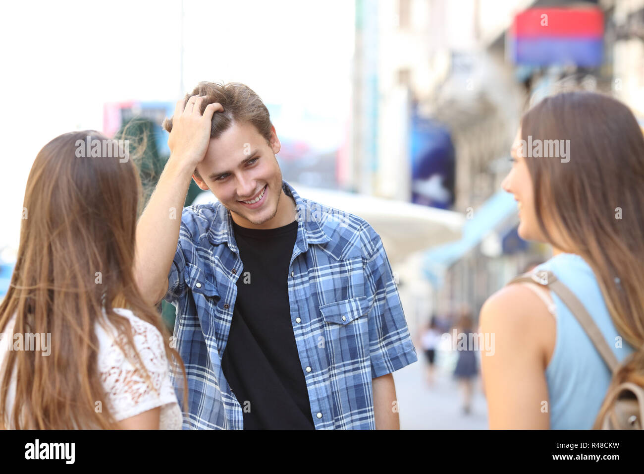 Young man flirting with two girls - Stock Image