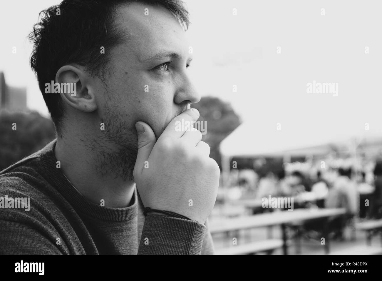 A handsome man looking off to the side in black and white - Stock Image