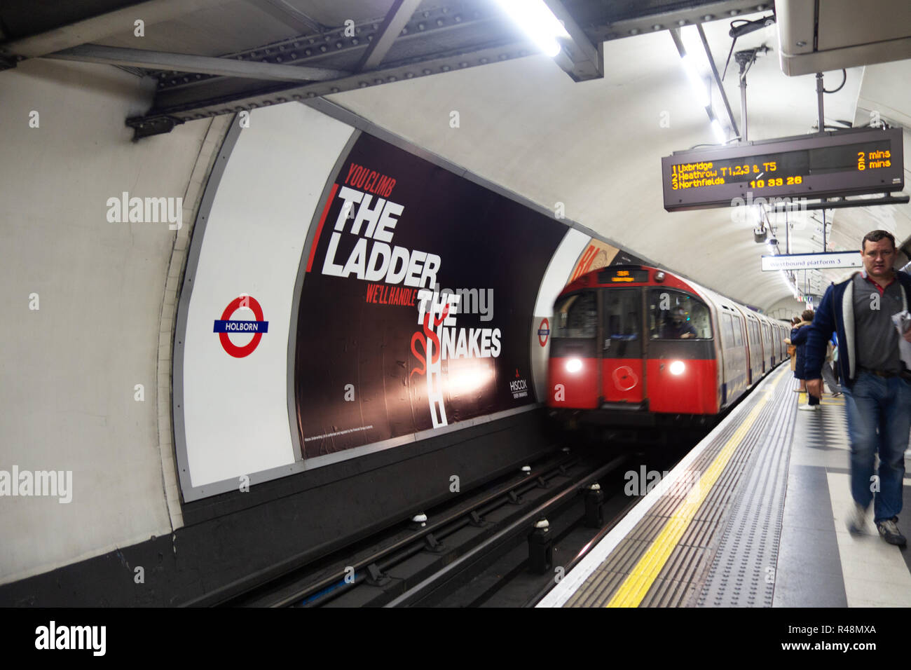 Tube train 48 sheet billboard poster Advertising poster next to the tracks on the London Underground track - Stock Image