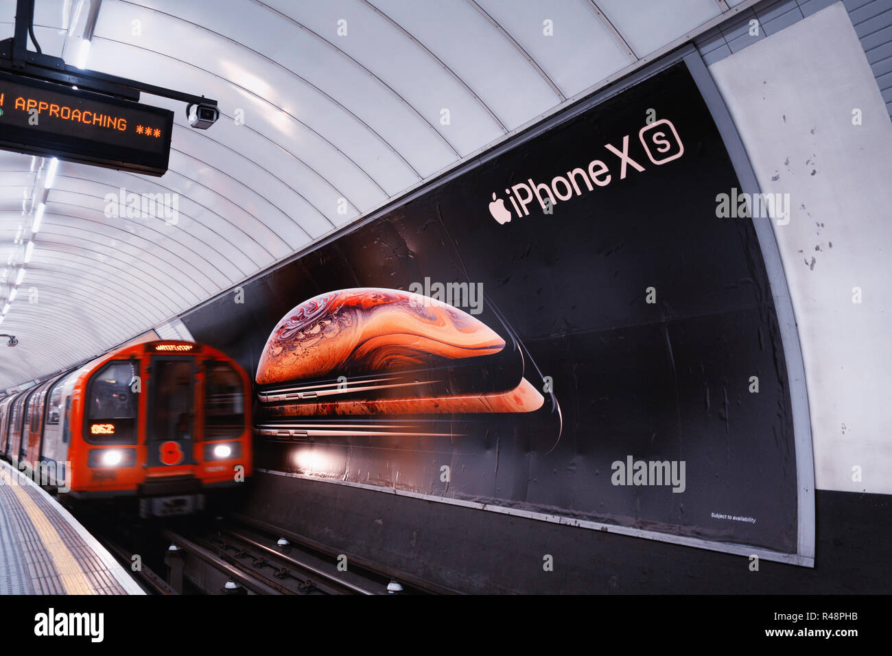 Tube train passing an ad poster for new Apple iPhone XS, advertising poster in the London Underground Track - Stock Image