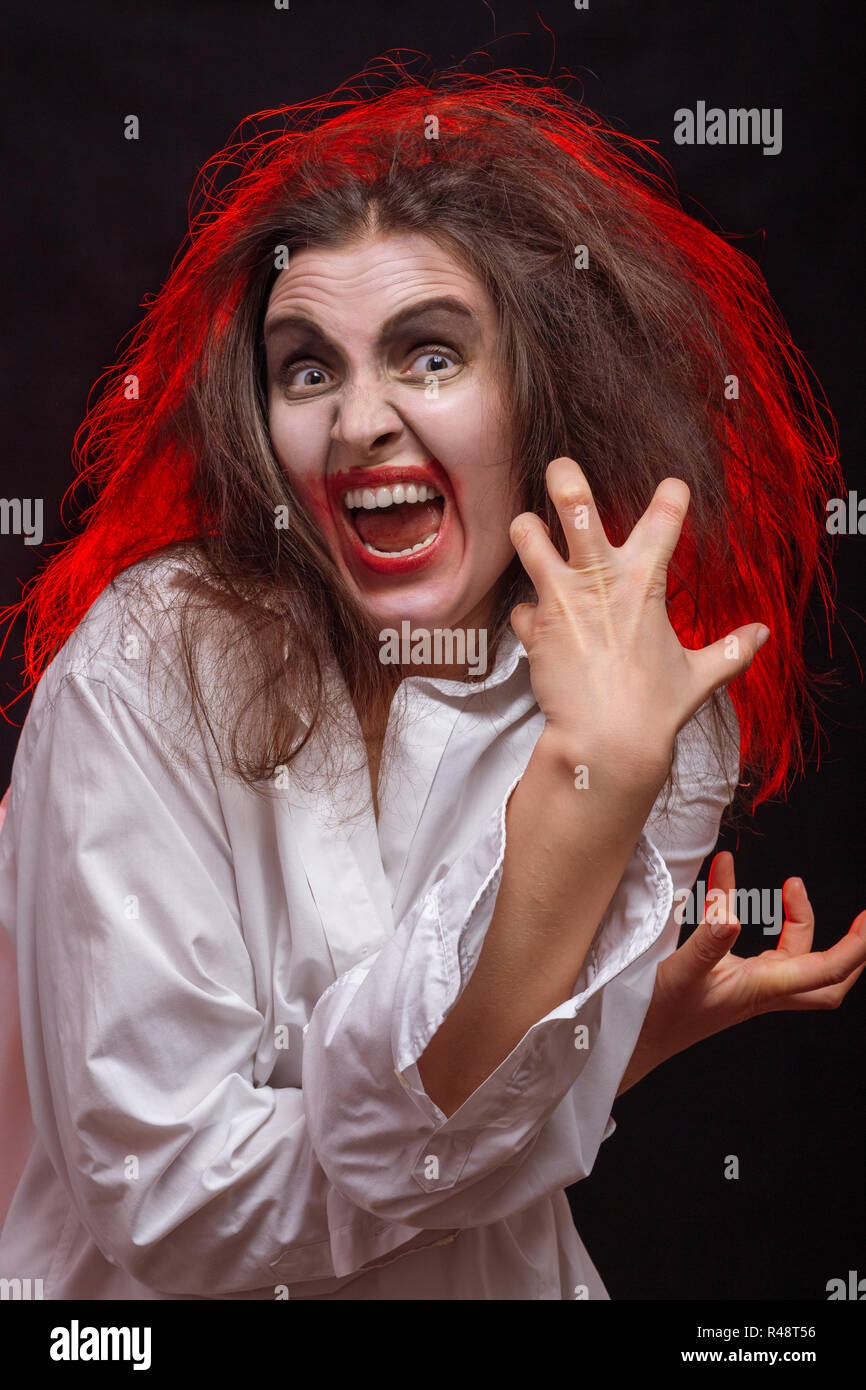 fun crazy young woman with fluffy hair on black background make grimace - Stock Image