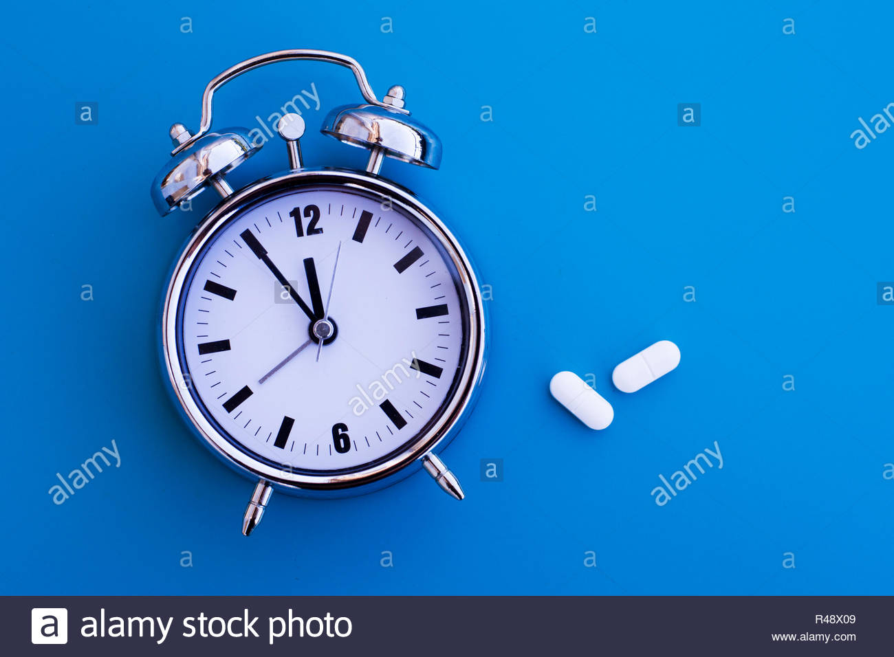 alarm clock with pills - Stock Image