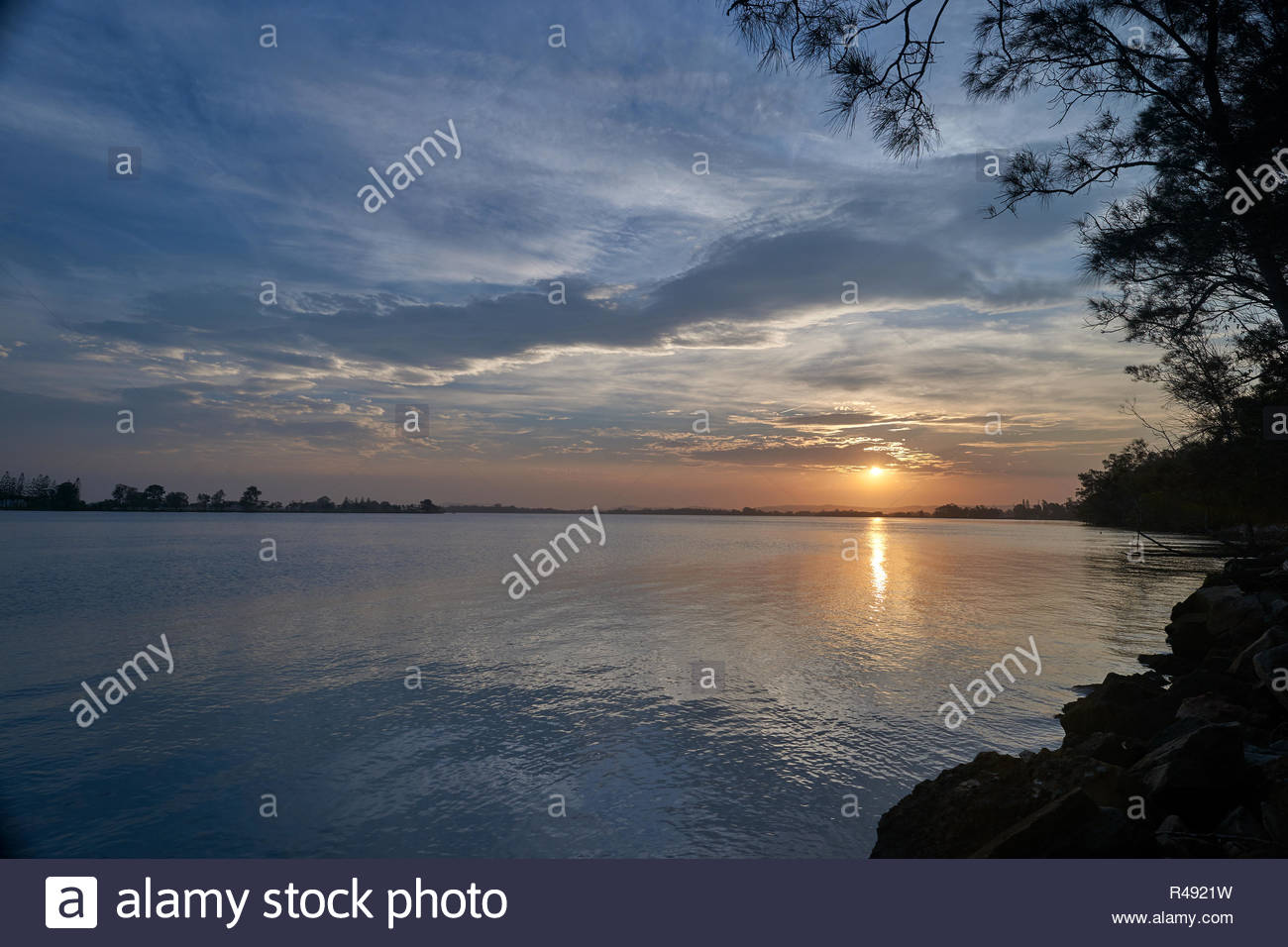 The colourful sky and water, of sunset over the Clarence River; taken from Goodwood Island - looking upstream - near Iluka and Yamba, NSW, Australia. - Stock Image